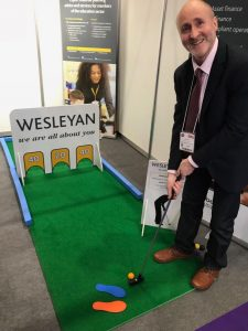 A simple minigolf hole in use at a trade show